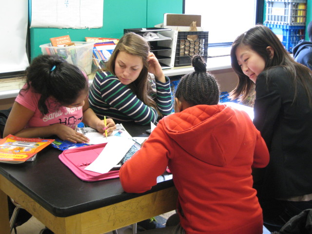 two students and their tutors in a classroom