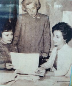 newsprint photograph of three women in 1966 looking together at a sheet of paper