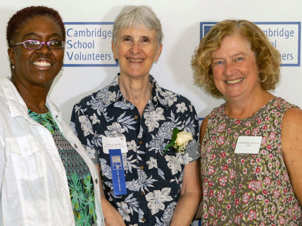 three women smiling middle woman wearing a blue ribbon